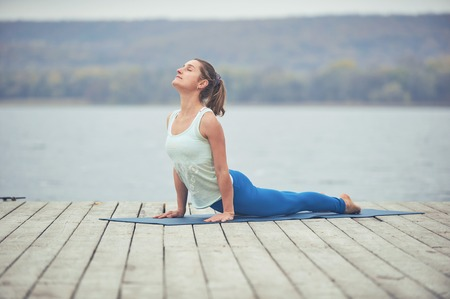 Photo for Beautiful young woman practices yoga asana upward facing dog on the wooden deck near the lake - Royalty Free Image
