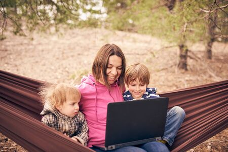 Foto de Working away from office concept, woman with two kids working on laptop while lying in hammock in a forest. - Imagen libre de derechos