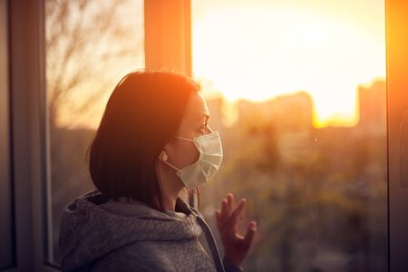 Foto de Woman near window at sunset in isolation at home for virus outbreak. Stay home concept. - Imagen libre de derechos
