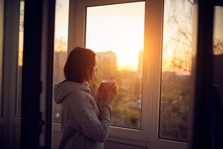 Photo pour Woman near window at sunset in isolation at home for virus outbreak. Stay home concept. - image libre de droit