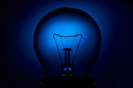 Photo for Electric bulb lamp with a spiral on a blue background. - Royalty Free Image