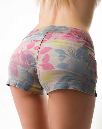 Foto de slim blondy girl in colored denim shorts - Imagen libre de derechos
