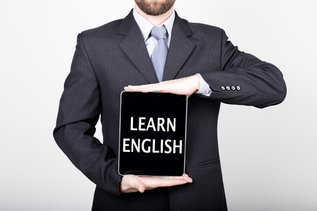 technology, internet and networking in business concept - businessman holding a tablet pc with learn english sign. Internet technologies in business.