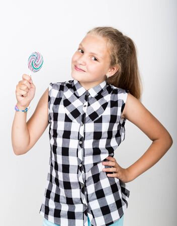 Portrait of happy beautiful young girl with sweet candys. pretty young girl dressed in a plaid shirt holding colorful lollipop.