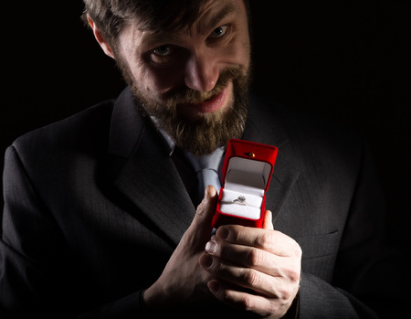 bearded man in a business suit gives a ring in the red box and expresses different emotions on a dark background.