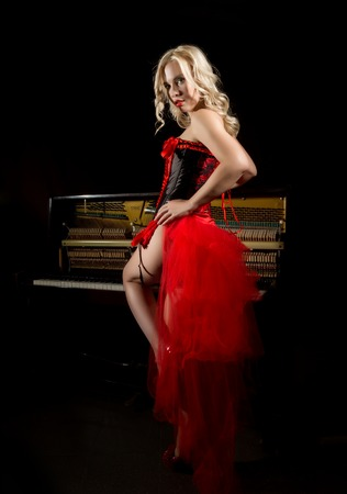 beautiful blonde musician in red corset standing near the piano. Vintage  style beautiful woman. f76f0d12f