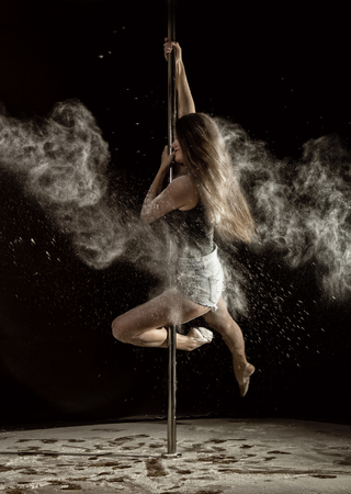 Beautiful expressive dencer dancing at studio with flour