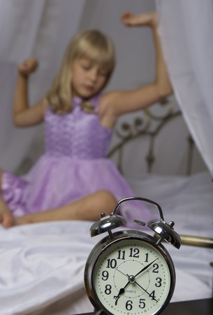 Alarm clock standing on bedside table. Wake up of an asleep young girl is stretching in bed in background