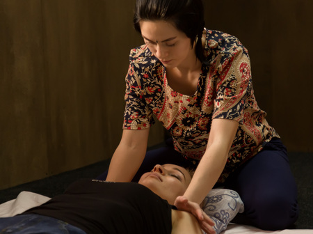 Masseur massaging back of female in spa resort, relaxed patient enjoys. Thai massage or Thai yoga massage treatment.