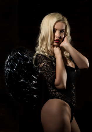 fallen black angel with wings. Sexual woman in black bodysuit and black wings on a black background.の写真素材