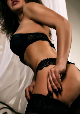 Photo pour seductive young woman with a beautiful body in black sexy lingerie - image libre de droit