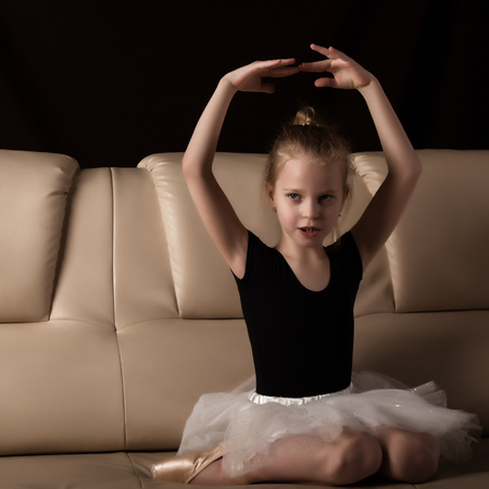 Photo for little ballerina in pointe sits and resting on the sofa. cute ballerina in the dance class is studying ballet. Classical dance, ballet - Royalty Free Image