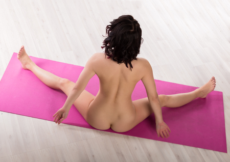 Foto de young seductive woman performs exercises in the nude. athletic woman on a light background - Imagen libre de derechos