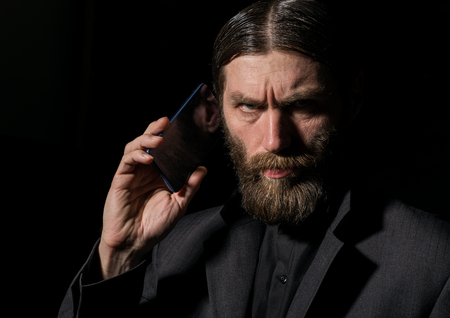 Photo pour Old believer senior priest with a smartphone, bearded old man is calling on a dark background - image libre de droit