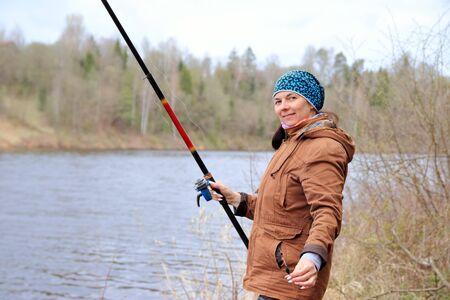 Photo pour woman with fishing rod on the river - image libre de droit