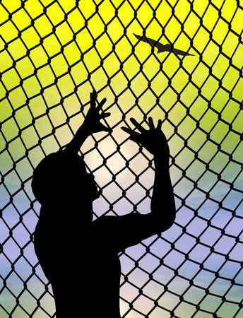 Desire for Freedom. Desperate prisoner or refugee behind a fence longing for to live a free life
