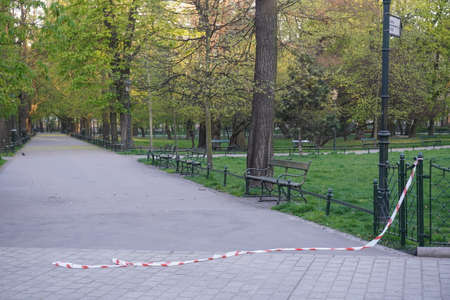 Poland, Cracow 20.04.20: Removing restrictions on visiting parks and forests, and Plenty Gardens during quarantine and coronavirus pandemic. barrier tape is torn and lies on path. Social distancing