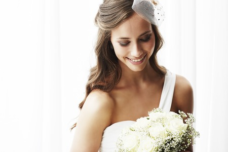 Foto de Young bride in wedding dress holding bouquet, studio shot - Imagen libre de derechos