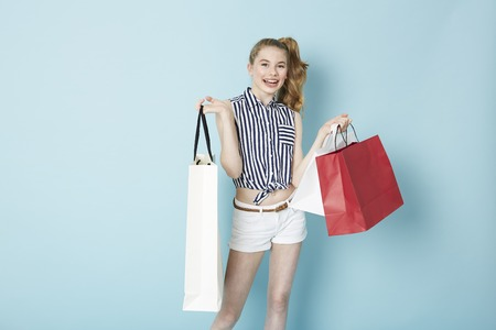 Joyful teenage girl with shopping bags
