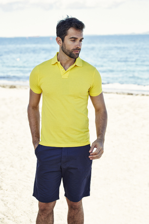 Guy in yellow shirt on beach, content