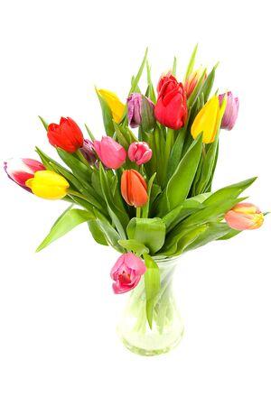 Foto de Colorful Dutch tulips in glass vase over white background - Imagen libre de derechos