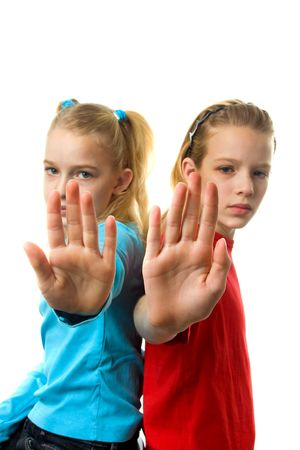 two caucasian girls making stop sign with hands over white background