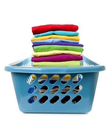 Laundry basket with folded clothes over white background