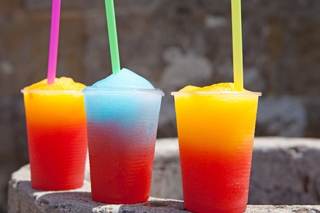 colorful slushy ice drinks in plastic cups