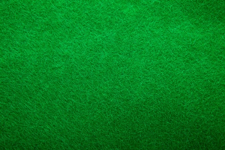 Background texture of green felt casino table in closeup