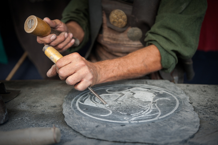 Photo pour Craftsman hands working on a slate plate - image libre de droit