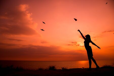 Photo pour Beautiful silhouette of young woman throwing paper airplane. - image libre de droit