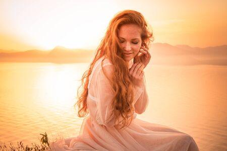 Foto de Young woman in long dress standing on a rock and looking to a sea - Imagen libre de derechos