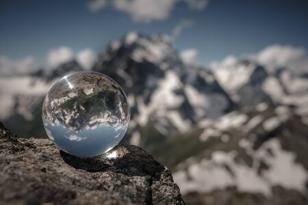 Photo pour Transparent glass sphere and snow-capped peaks in the background. Concept and idea of travel - image libre de droit