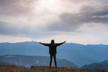 Photo pour Landscape with silhouette of a standing happy man and raised-up arms on the mountain peak on the background of cloudy sky. autumn rain in the mountains - image libre de droit
