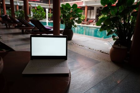 Foto de A white laptop on wooden table swiming pool background. A start of new day. Freelance business concept. Flexible remote working, travelling, advert and copy space - Imagen libre de derechos