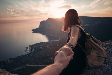 Photo pour Girl standing on the mountain top over blue sea view. Follow me - POV. Couple enjoying a hike in nature. The concept of the journey to the meeting of new discoveries - image libre de droit