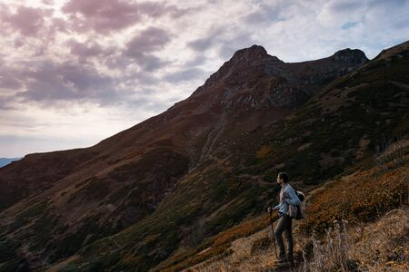 Photo for Young male hipster in the mountains in autumn. Discovery Travel Destination Concept. Tourist on the high rocks background. Sport and active life concept. - Royalty Free Image