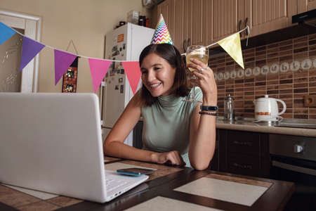 Foto de Asian woman virtual happy hour meeting birthday party with cake online, together with her friend in video conference with laptop for online meeting in video call , for social distancing - Imagen libre de derechos