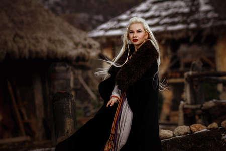 Photo pour Beautiful blonde Viking dressed in a black cloak against the backdrop of the castle. beautiful film set - an ancient Viking village - image libre de droit