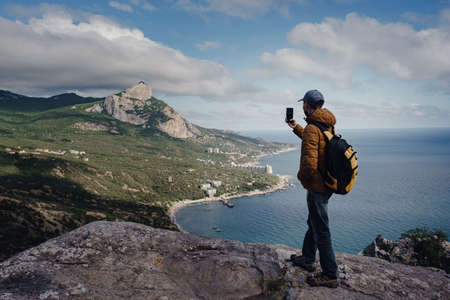 Photo for man taking photo of awesome view of mountains with smartphone. travel and discovery concept - Royalty Free Image
