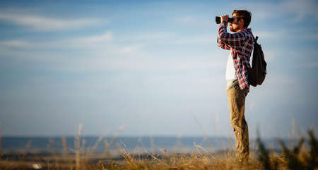 Photo pour Guy looking at binoculars in hill. man in t-shirt with backpack. Young Caucasian man during hike in valley landscape - image libre de droit