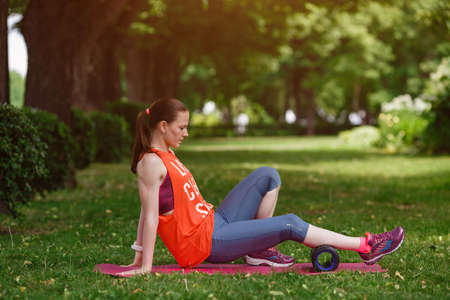 Foto de Young beautiful woman meditates on a summer day in the park. Idea and concept of calm in a busy city and a healthy lifestyle, stretching and preparing for a run in the park - Imagen libre de derechos
