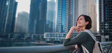 Photo pour Happy young female traveler in the big city of Dubai, famous place Dubai marina. Luxury and comfortable tourism season in United Arab Emirates. - image libre de droit