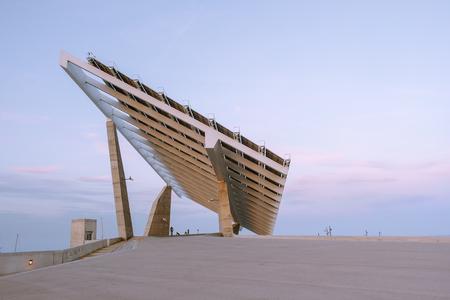 Foto de Side view of contemporary big diagonal construction with solar batteries on concrete passage against blue sky - Imagen libre de derechos