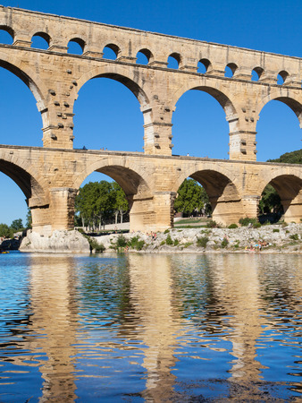 Pont du Gard reflected in the waters of Gardon river in Languedoc-Roussillon, France