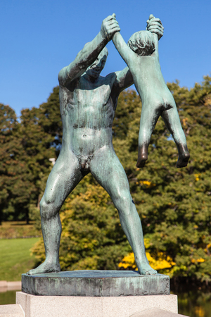 Oslo, Norway - September 16, 2017: 'Man Swinging Boy' at Vigeland Park in Oslo, Norway, sculpted in bronze by Gustav Vigeland in 1930.