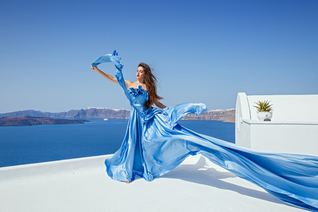 Photo pour Young beautiful woman in blue dress against the sea and the island of Santorini, Greece - image libre de droit