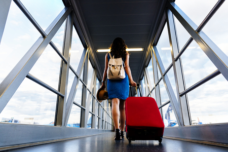 Photo pour Young girl traveler walking with carrying hold suitcase in the airport. Tourist Concept. - image libre de droit