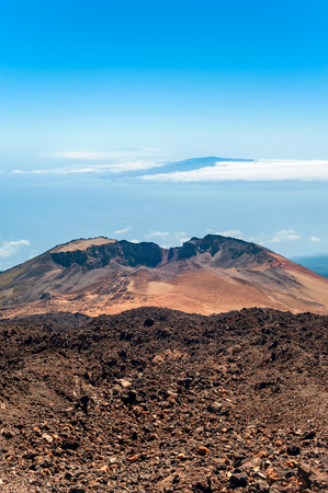 Over the Horizon. Crater of Pico Viejo volcano on a blue cloudscape background. Canary Islands, Tenerife, Spain. Multicolored outdoors image.