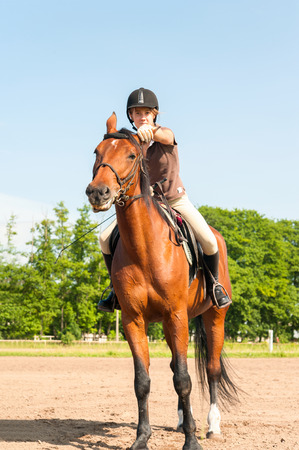 Young teenage girl equestrian riding horseback on chestnut horse. Multicolored outdoors vertical image.